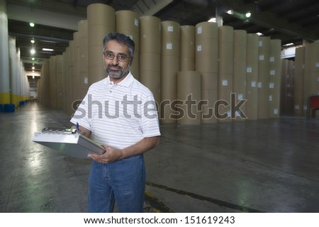 Portrait of a male work against huge rolls of paper in newspaper factory