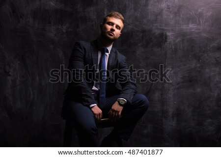 Portrait of a man sitting on a chair against a background of chalkboard