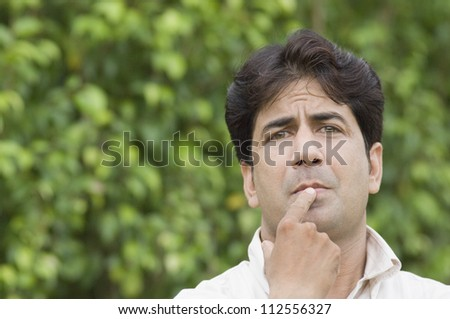 Portrait of a man thinking in a park