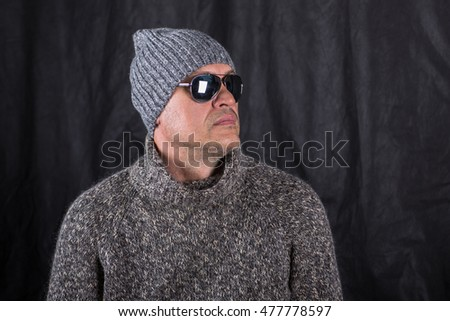portrait of a man wearing glasses and a sweater and winter hat in the studio