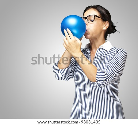 portrait of a middle aged woman blowing a balloon against a grey background