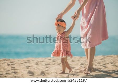 portrait of a mother is teaching her daughter walks on the beach