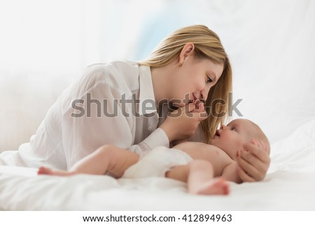 Portrait of a mother with her newborn baby in white bedroom