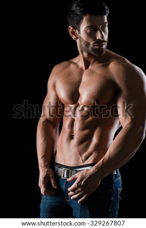 Portrait of a muscular man looking away over black background