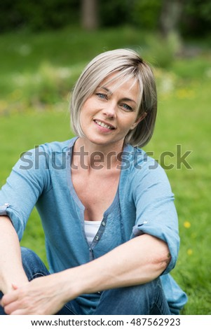 portrait of a nice woman of forty years old with grey hair. she is sitting in the grass , in the park. she does a break and she is happy , it 's  summer. the background is blur