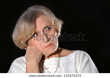 portrait of a pensive woman in white on a black background