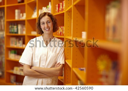 Portrait of a pharmacist leaning on shelves in pharmacy