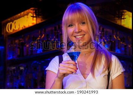 portrait of a pretty blond girl smiling and drinking in a bar