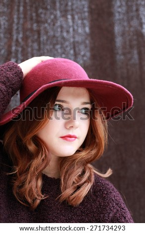 Portrait of a pretty teenage girl with red hair and floppy hat