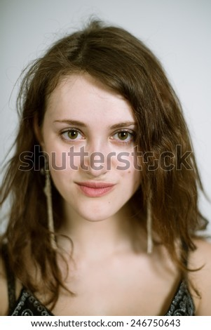 Portrait of a real young woman on a light background in a black dress. Shallow depth of field. Focus on the eyelashes