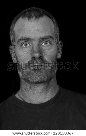 portrait of a rugged grizzled middle aged man with black t-shirt on black background processed to show skin texture and flaws