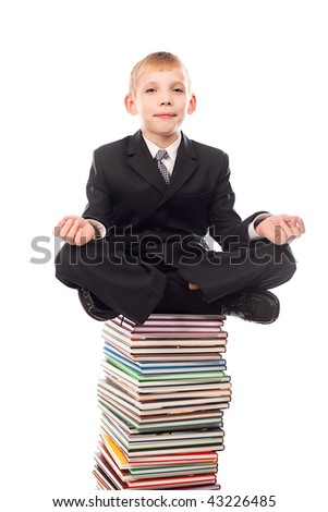 Portrait of a schoolboy sitting on a stack of books.