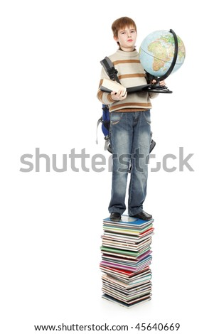 Portrait of a scoolboy standing on a stack of books.