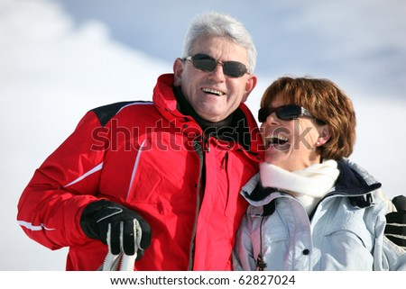 Portrait of a senior man and a senior woman smiling in snow