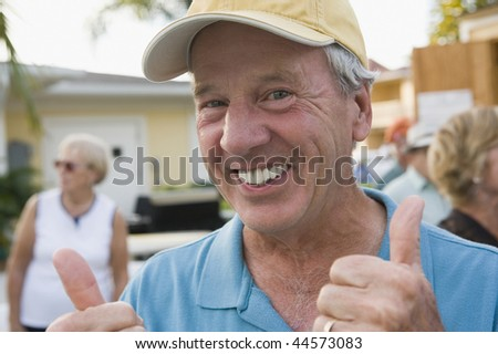 Portrait of a senior man showing a thumbs up sign and smiling