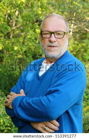 Portrait of a senior man with blue shirt and black glasses