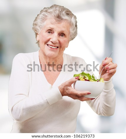 portrait of a senior woman eating salad indoor