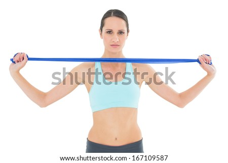 Portrait of a serious fit young woman holding blue yoga belt over white background