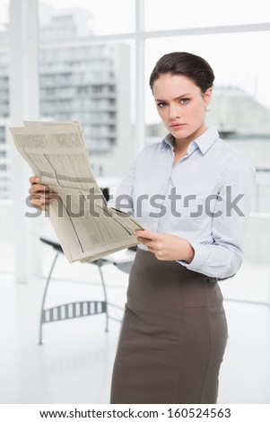 Portrait of a serious young businesswoman with newspaper in a bright office