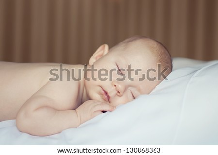 portrait of a small sleeping baby curled up