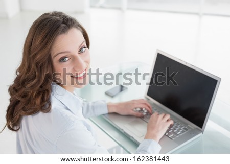 Portrait of a smiling brown haired businesswoman using laptop in a bright office