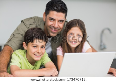 Portrait of a smiling father with young kids using laptop in the kitchen at home
