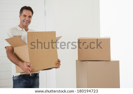 Portrait of a smiling man carrying boxes in new house