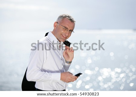 Portrait of a smiling man in suit with a phone
