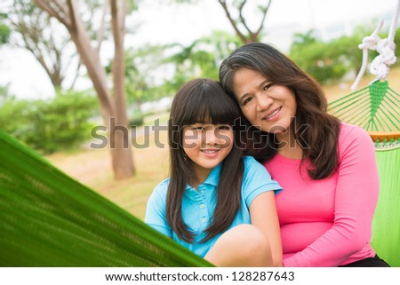 Portrait of a smiling mother and a daughter embracing and looking at camera