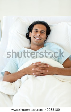Portrait of a smiling patient lying in a hospital bed. Medical concept.