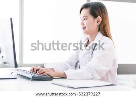 Portrait of a smiling physician working in her office. Asia