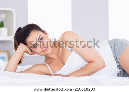 Portrait of a smiling relaxed young woman lying in bed at home