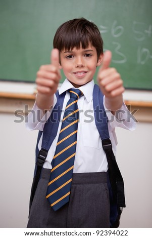 Portrait of a smiling schoolboy with the thumbs up in a classroom