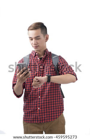 Portrait of a smiling student looking on cellphone and wrist watch over white  background