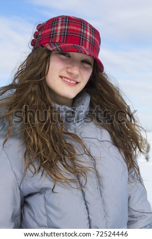 Portrait of a smiling teenager with red cap and grey winter jacket