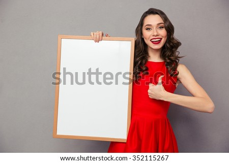 Portrait of a smiling woman holding blank board and showing thumb up over gray background