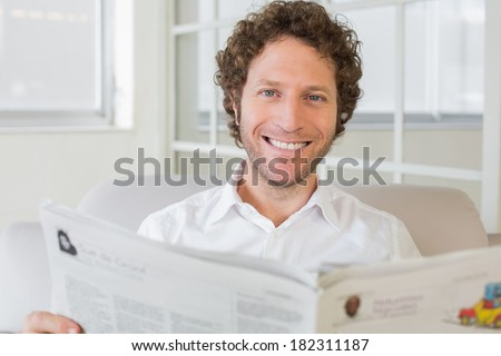 Portrait of a smiling young man reading newspaper on sofa in the house