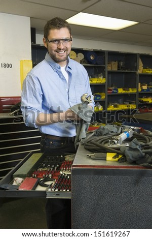 Portrait of a smiling young man with tools working in workshop