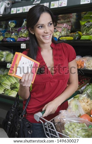 Portrait of a smiling young woman food shopping in supermarket