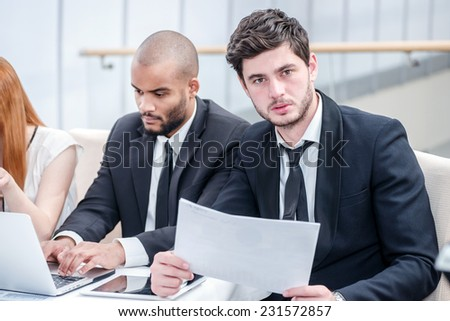 Portrait of a successful businessman. Four successful businessman sitting at the table at a business meeting in the office and looking at the laptop up while discussing business matters