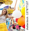 Portrait of a teenage girl visiting a fun fair ground with rides and lights around her, holding balloons being playful and joyful during a fun day. - stock photo