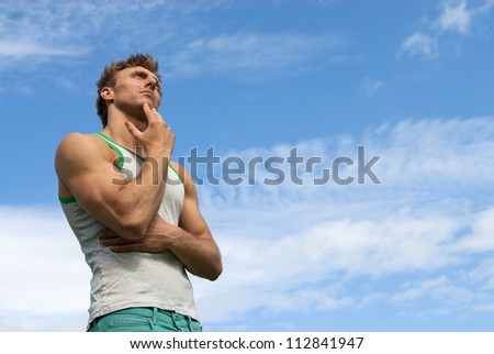 Portrait of a thoughtful strong man, on blue sky background.