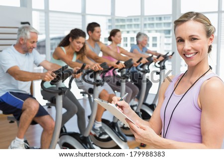Portrait of a trainer with people working out at exercise class in gym