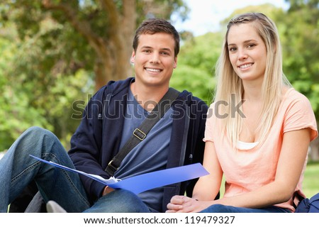 Portrait of a tutor helping a teenager to revise in a park