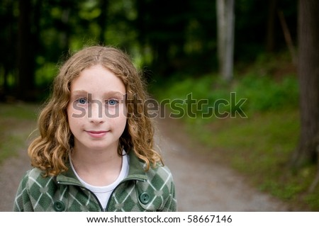 portrait of a tween aged girl outdoors looking at the camera