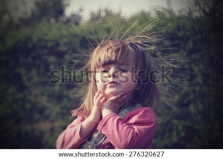 Portrait of a two-year girl with disheveled hair on the trampoline Vintage