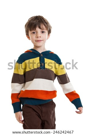 Portrait of a 6 year old boy standing wearing a sweater, waist up isolated on a white background