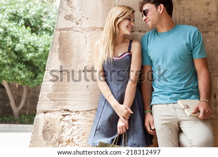 Portrait of a young and attractive romantic tourist couple enjoying a day out together sightseeing, smiling against an old stone wall and carrying shopping bags. Romantic travel and relationships.
