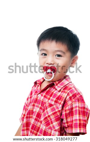 Portrait of a young Asian boy with pacifier in mouth over white background.