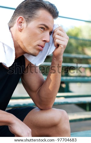 Portrait of a young athletic man with workout towel